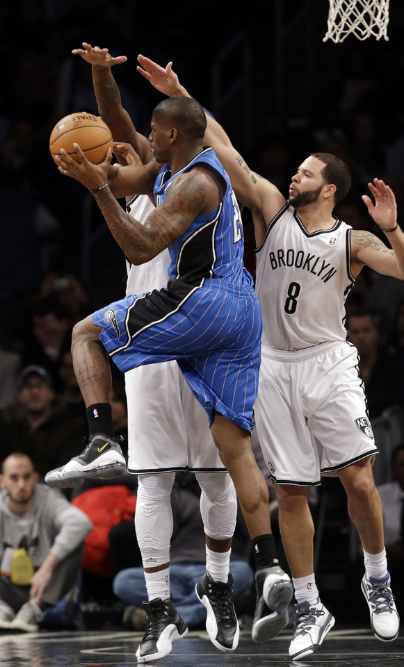 Orlando Magic forward DeQuan Jones (20)  passes as he is double-teamed by Brooklyn Nets guard Deron Williams (8) and Brooklyn Nets forward Andray Blatche (0) in the first half of their NBA basketball game at the Barclays Center, Monday, Jan. 28, 2013 in New York. (AP Photo/Kathy Willens)