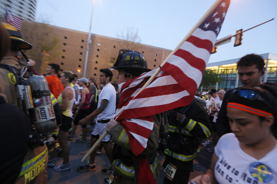 Photo - A fireman carries an American flag at the start of the Oklahoma City Memorial Marathon in Oklahoma City, Sunday, April 28, 2013.  Photo by Garett Fisbeck, For The Oklahoman