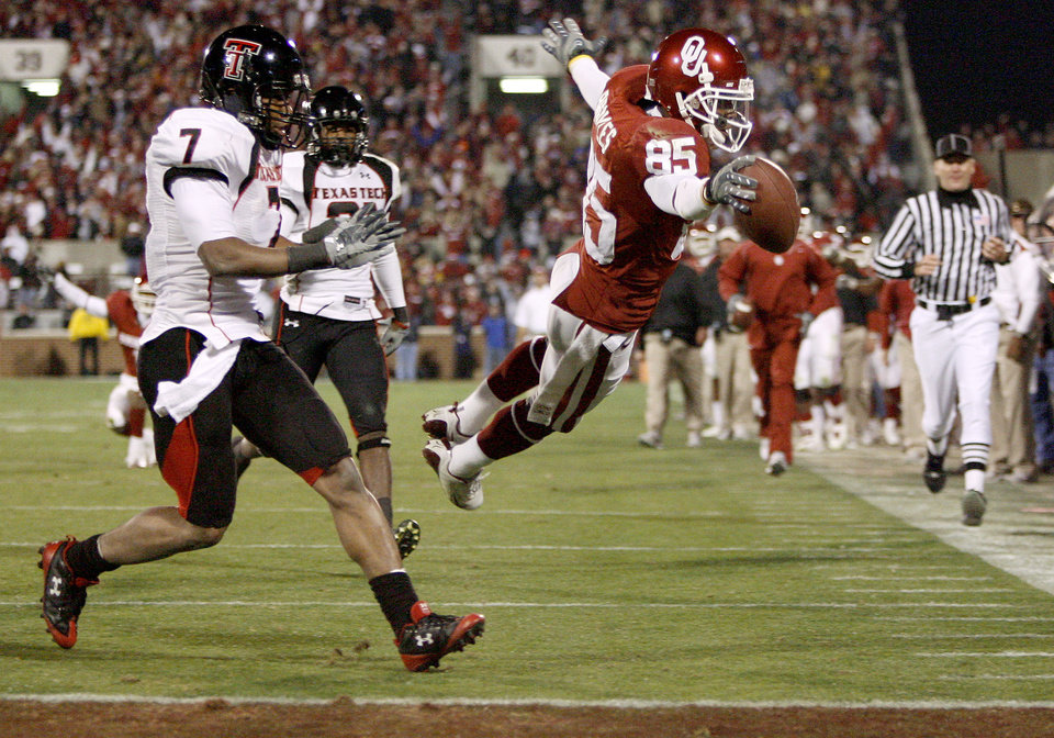 Photo - OU's Ryan Broyles dives for a touchdown past Darcel McBath, left, and L.A. Reed during the college football game between the University of Oklahoma Sooners and Texas Tech University at Gaylord Family -- Oklahoma Memorial Stadium in Norman, Okla., Saturday, Nov. 22, 2008. BY BRYAN TERRY, THE OKLAHOMAN