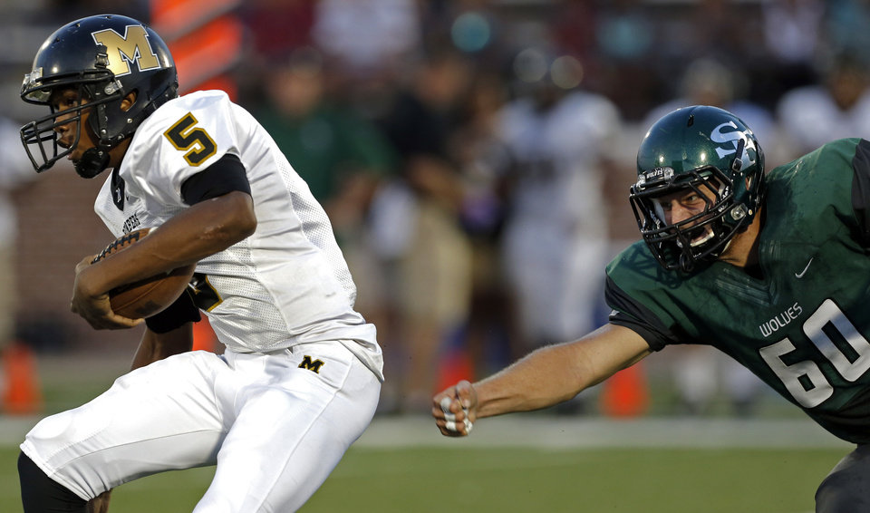Photo - Midwest City's Aaron McKinney gets by Edmond Santa Fe's Hayden Ball during the high school football game between Edmond Santa Fe and Midwest City at Wantland Stadium in Edmond, Okla., Thursday, Sept. 5, 2013. Photo by Sarah Phipps, The Oklahoman