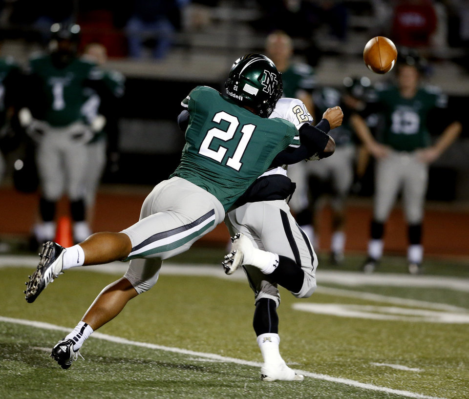 Photo - Norman North's D. J. Hicks knocks the ball from the grasp of Broken Arrow receiver Austin Reed after a long pass reception in class 6A football on Friday, Nov. 16, 2012 in Norman, Okla.  The fumble was recovered by a Broken Arrow player.  Photo by Steve Sisney, The Oklahoman