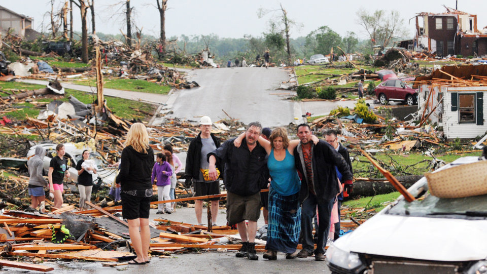 Residents of Joplin, Mo, help a woman who survived in her basement after a tornado hit the city on Sunday, May 22, 2011. The tornado tore a path a mile wide and four miles long destroying homes and businesses. (AP Photo/Mike Gullett) ORG XMIT: MOMG102