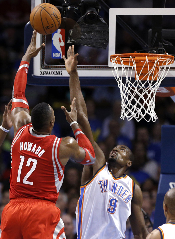 Photo - Oklahoma City's Serge Ibaka (9) defends against Houston's Dwight Howard (12) during the NBA game between the Oklahoma City Thunder and Houston Rockets at the  Chesapeake Energy Arena  in Oklahoma City, Okla., Tuesday, March 11, 2014. Photo by Sarah Phipps, The Oklahoman