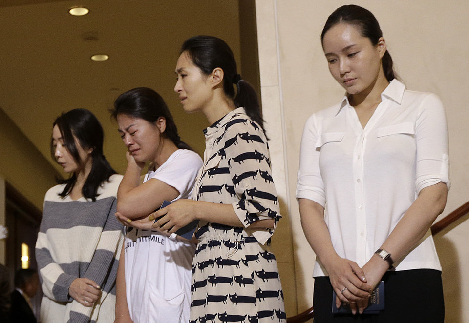 Photo - Lee Yoon-hye, center, cabin manager of Asiana Flight 214, which crashed on Saturday, July 6, 2013, and other flight attendants appear at a news conference at San Francisco International Airport in San Francisco, Wednesday, July 10, 2013. Two passengers were killed and many others were injured in the crash. (AP Photo/Jeff Chiu)