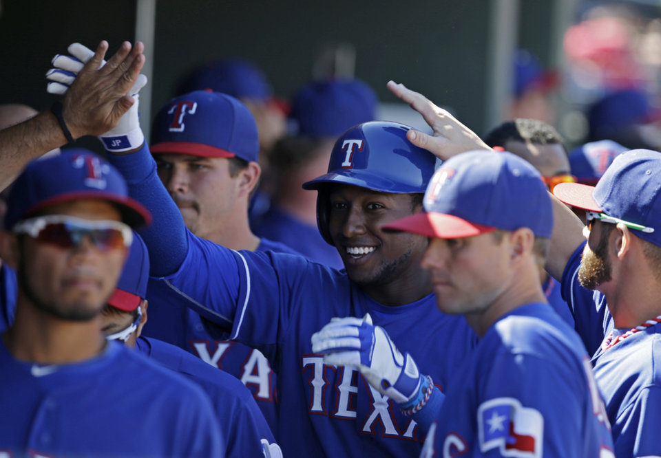Photo - Texas Rangers' Jurickson Profar is congratulated in the dugout after hitting a solo home run during the third inning of a spring exhibition baseball game, Monday, March 10, 2014, in Suprise, Ariz. (AP Photo/Darron Cummings)