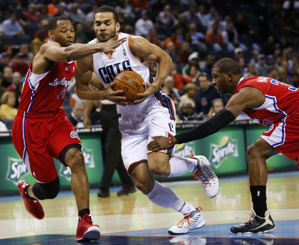 Photo - Charlotte Bobcats' Ramon Sessions, center, is fouled as he drives between Los Angeles Clippers' Chris Paul, right, and Willie Green, left, during the first half of an NBA basketball game in Charlotte, N.C., Wednesday, Dec. 12, 2012. (AP Photo/Chuck Burton)