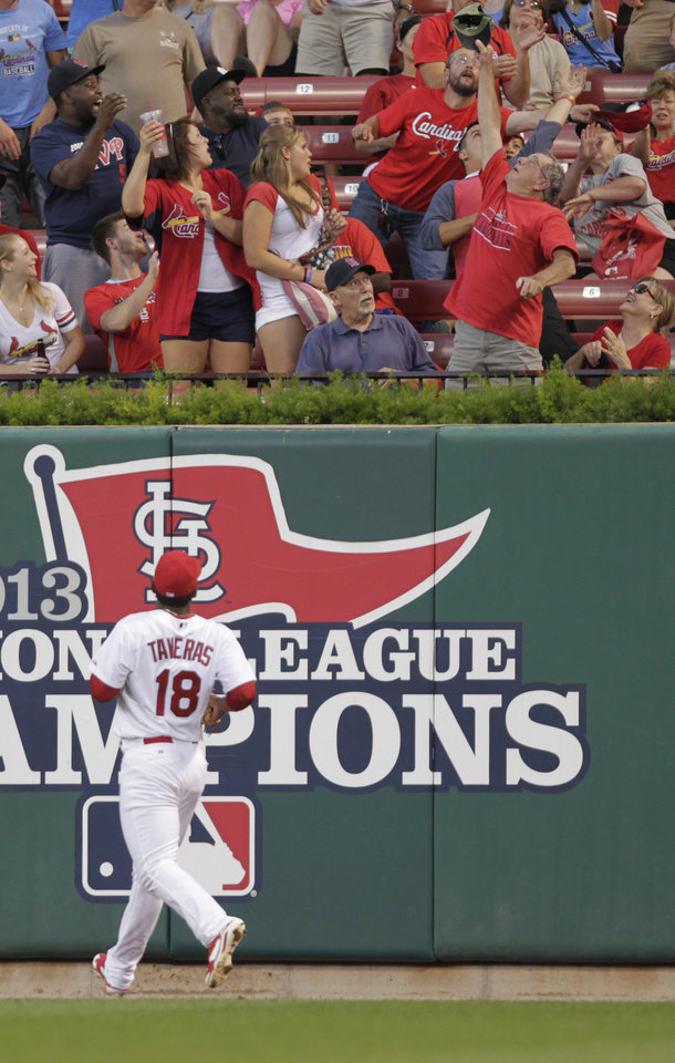 Photo - St. Louis Cardinals right fielder Oscar Taveras (18) watches a fan catch a home run ball, hit by Pittsburgh Pirates' Pedro Alvarez, in his hat in the fourth inning of a baseball game, Tuesday, July 8, 2014 in St. Louis. (AP Photo/Tom Gannam)