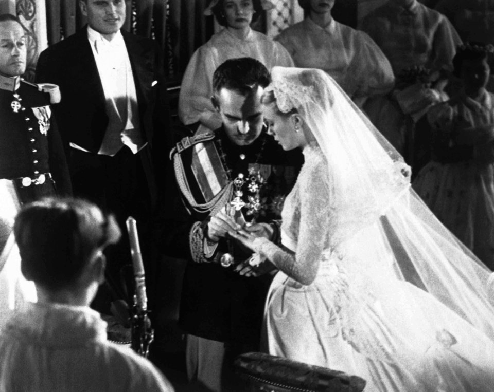 Photo - ILE-   This April 19, 1956 file photo shows Prince Rainier as he places the ring on Grace Kellyís finger during their wedding ceremony, in Monaco Cathedral. Kelly's gown, made by costumer Helen Rose and the wardrobe department of MGM, was