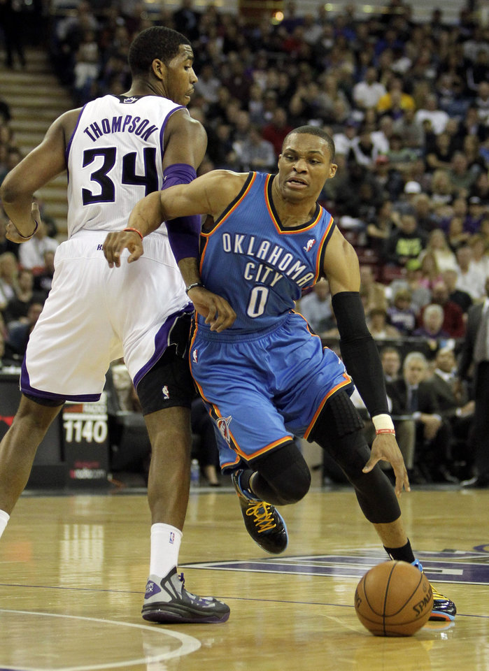 Photo - Oklahoma City Thunder guard Russell Westbrook, right, drives past Sacramento Kings forward Jason Thompson during the first quarter of  an NBA basketball game in Sacramento, Calif., Friday, Jan. 25, 2013. (AP Photo/Rich Pedroncelli)