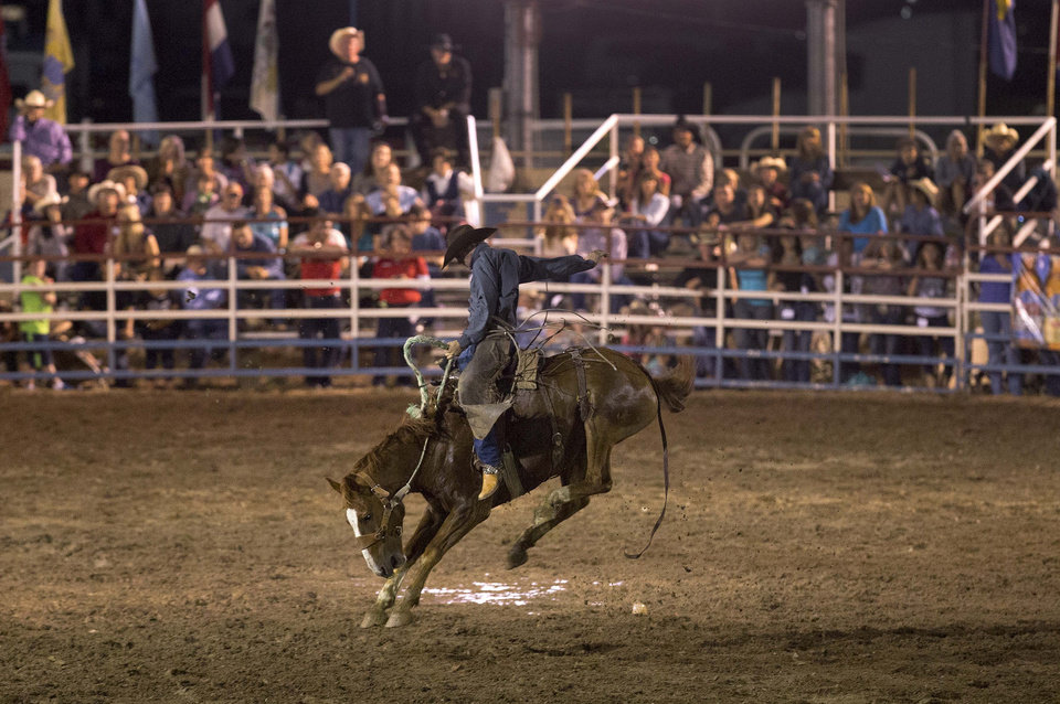 A cowboy competes in the saddle bronc competition during the Prescott Frontier Days Rodeo, Wednesday, July 3, 2013 in Prescott, Ariz. A mile-high city about 90 miles northwest of Phoenix, Prescott remains a modern-day outpost of the pioneer spirit. It\'s that spirit that will guide officials as they navigate the days ahead and figure out how to honor the elite Hotshot firefighters who died in a nearby wind-driven wildfire that is still burning. (AP Photo/Julie Jacobson)