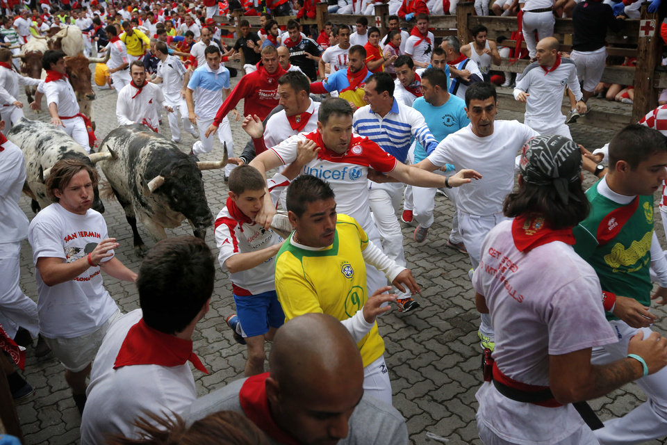 Photo - Revelers are chased by fighting bulls during the running of the bulls of the San Fermin festival, in Pamplona, Spain, Monday, July 7, 2014. Revelers from around the world arrive here to take part in the eight-day event glorified by Ernest Hemingway's 1926 novel