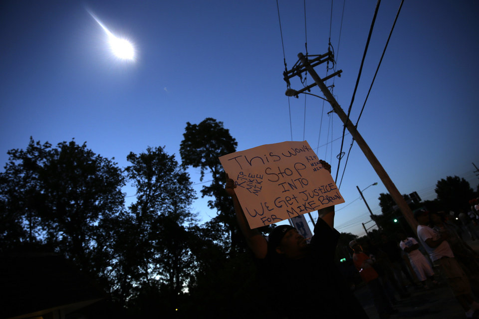 Photo - A protester holds up a sign as a police helicopter circles overhead Wednesday, Aug. 13, 2014, in Ferguson, Mo. Protests in the St. Louis suburb rocked by racial unrest since a white police officer shot an unarmed black teenager to death turned violent Wednesday night, with some people lobbing Molotov cocktails and other objects at police who responded with smoke bombs and tear gas to disperse the crowd. (AP Photo/Jeff Roberson)