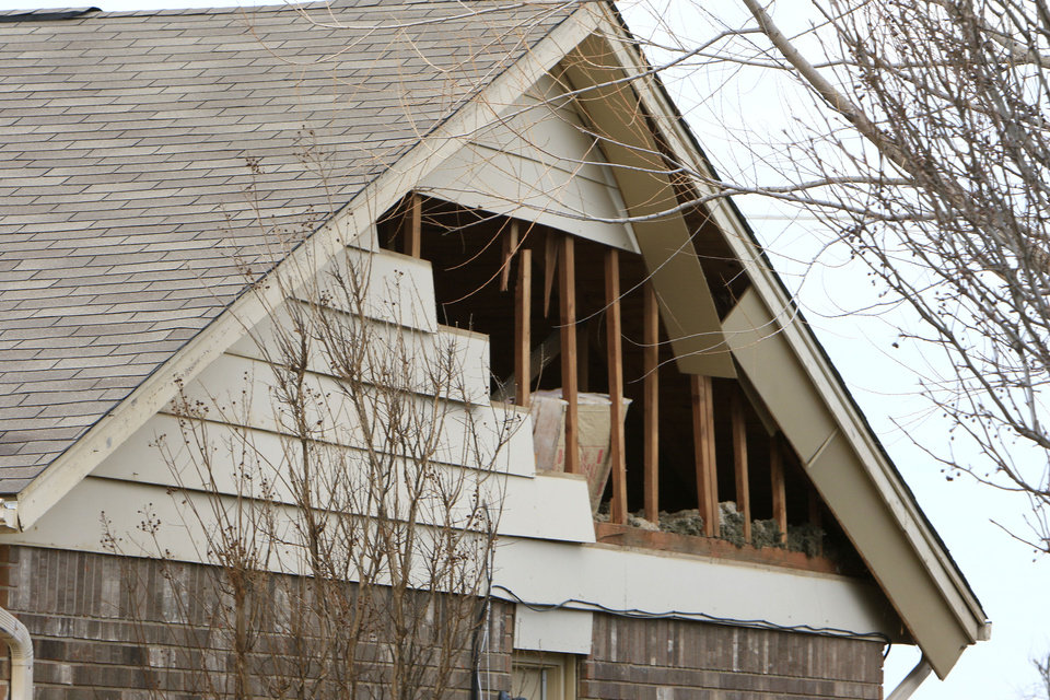 Photo - The gable end of a house is badly damaged, five doors away from a house which exploded at 12409 Whispering Hollow Drive in Oklahoma City, OK, Saturday, January 2, 2016. The cause of the explosion is being investigated. Photo by Paul Hellstern, The Oklahoman