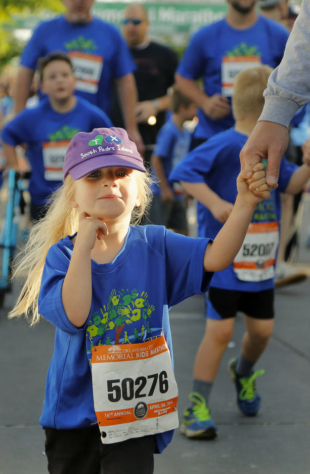 Photo - Addison Day, holds her dad's hand as she participates in the kid's marathon during the Oklahoma Memorial Marathon in Oklahoma City, Okla. on Sunday, April 24, 2016.   Photo by Chris Landsberger, The Oklahoman