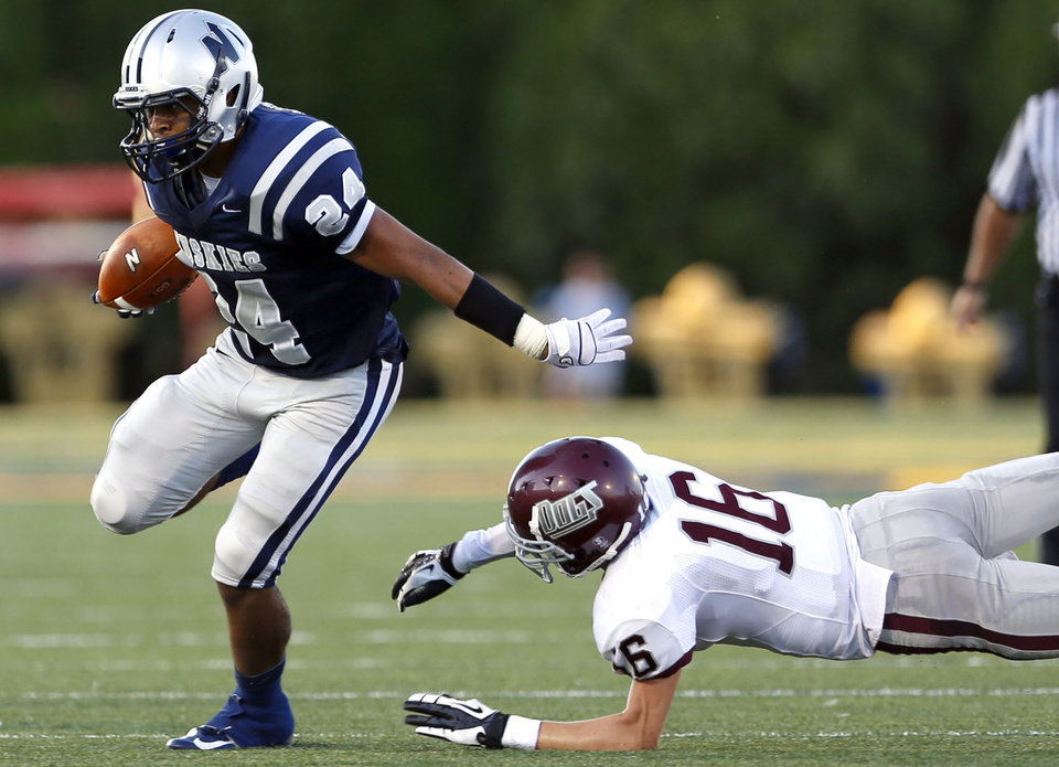 Photo - Edmond North's Ezel McIntee gets by Edmond Memorial's Tasdem Ingram during the high school football game between Edmond North and Edmond Memorial at Wantland Stadium in Edmond, Okla., Friday, Aug. 31, 2012. Photo by Sarah Phipps, The Oklahoman