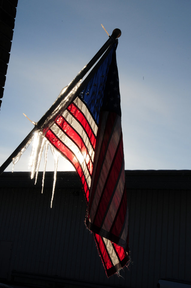 Icicles form on a U.S. flag located under melting snow on the roof of a store in Baxter, Minn. on Wednesday, Dec. 26, 2012. Cold temperatures are beginning to ease in Central Minnesota after a Christmas holiday with temperatures dipping below zero. (AP Photo/Brainerd Dispatch, Steve Kohls)