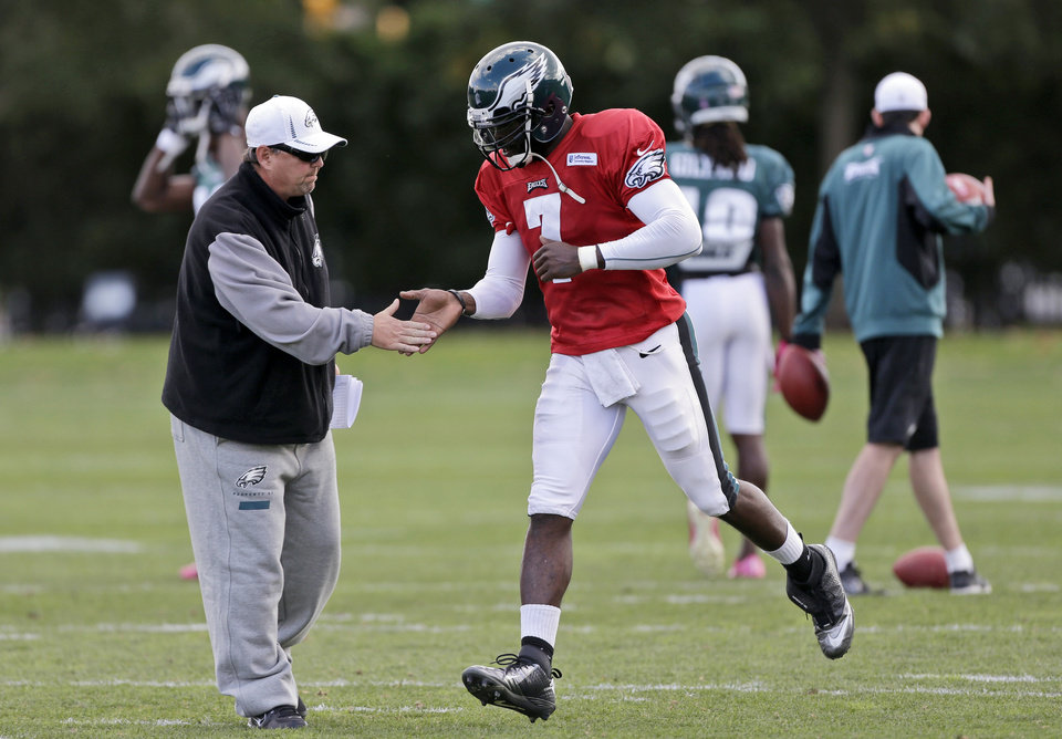 Philadelphia Eagles quarterback Michael Vick, center, shakes hands with offensive coordinator Marty Mornhinweg during practice at the team's NFL football training facility, Wednesday, Oct. 10, 2012, in Philadelphia. (AP Photo/Matt Rourke)