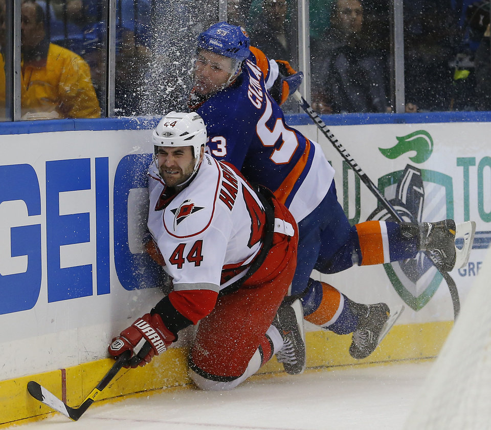 Carolina Hurricanes defenseman Jay Harrison (44) is checked into the boards by New York Islanders center Casey Cizikas (53) during the second period of an NHL hockey game at the Nassau Coliseum in Uniondale, N.Y., Monday, Feb.11, 2013. (AP Photo/Paul J. Bereswill)
