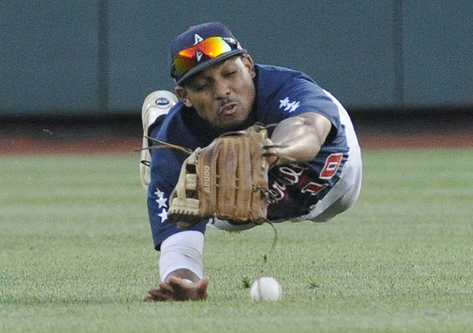 Photo - Vanderbilt center fielder John Norwood dives and misses the ball hit by Virginia third baseman Kenny Towns in the third inning of game one of the best-of-three NCAA baseball College World Series finals in Omaha, Neb., Monday, June 23, 2014. (AP Photo/Eric Francis)