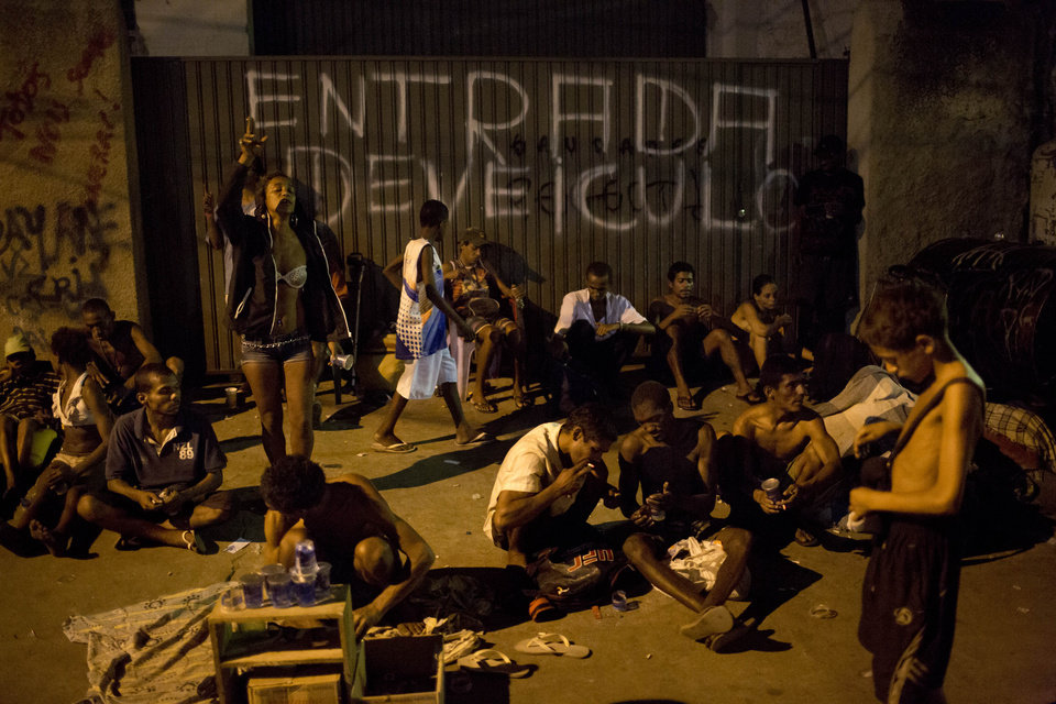 "Photo - A woman, left, stands as she sings with members of the 'Paz e Vida' christian church as other drug users gather in a ""cracolandia,"" or crack land in a northern slum of Rio de Janeiro, Brazil, Thursday, Oct. 24, 2013. Members of the non-governmental agency Anjos da Liberdade and of the 'Paz e Vida' Christian church visited one of the most populated crack lands in Rio where they sang, distributed food, soda and chocolate to the drug users living there. The main goal of the visit is to convince users to become drug free, reenter society and become productive workers. (AP Photo/Felipe Dana)"