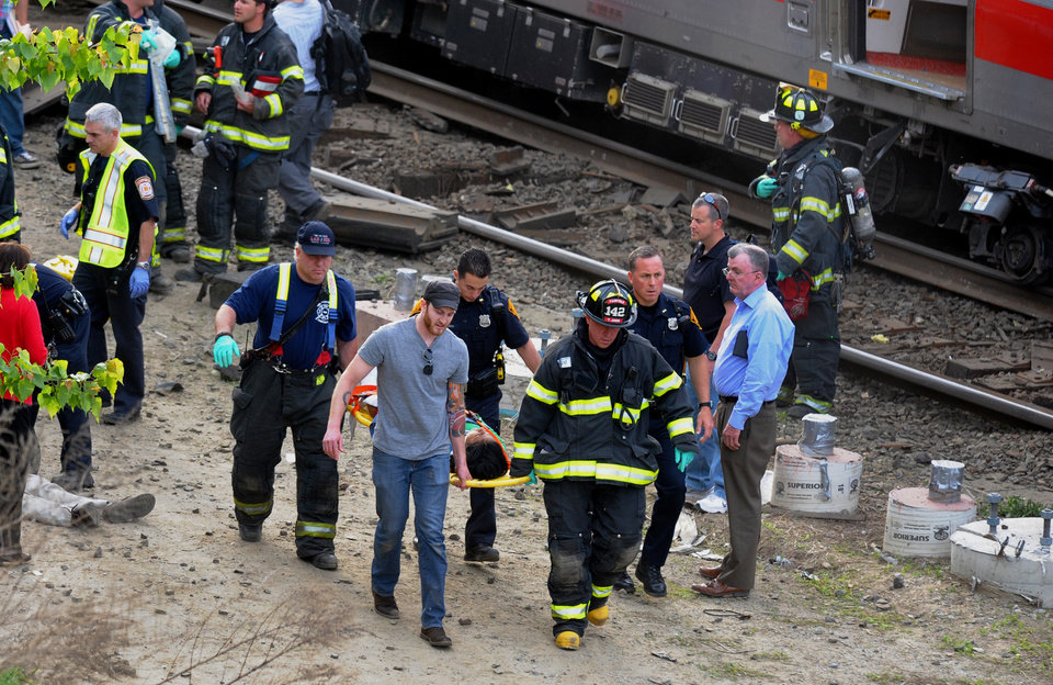 Photo - Injured passengers are transported from the scene where two Metro North commuter trains collided, Friday, May 17, 2013 near Fairfield, Conn. Bill Kaempffer, a spokesman for Bridgeport public safety, told The Associated Press approximately 49 people were injured, including four with serious injuries. About 250 people were on board the two trains, he said. (AP Photo/The Connecticut Post, Christian Abraham) MANDATORY CREDIT: CONNECTICUT POST, CHRISTIAN ABRAHAM