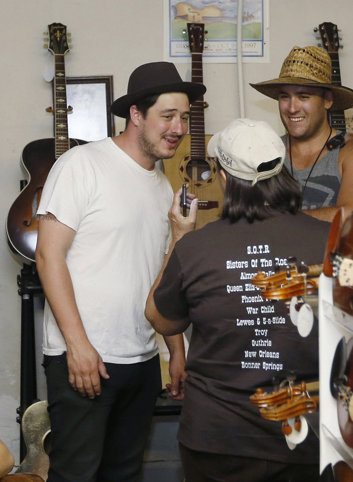 In this Sept. 5, 2013, photo Marcus Mumford, of the band Mumford & Sons, talks with Lucy Swanson, center, executive assistant for the Guthrie Chamber of Commerce, as he visits the Double Stop Fiddle Shop in Guthrie,, Okla. The population of the small Oklahoma town is expected to quadruple this weekend as people come to watch the British folk rock band on the second stop of the Mumford & SonsÂ' Gentlemen of the Road concert series in Guthrie. At right is Kevin Bilvin. (AP Photo/Sue Ogrocki) ORG XMIT: OKSO103
