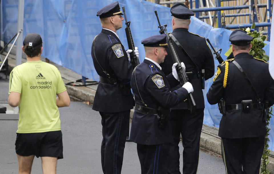 Photo - A runner passes as Boston Police honors change their post outside the Marathon Sports store, the site of the first of two bombs that exploded near the finish line of the 2013 Boston Marathon, Tuesday, April 15, 2014 in Boston. Three were killed and more than 260 injured in last year's explosions near the finish line of the race. (AP Photo/Charles Krupa)