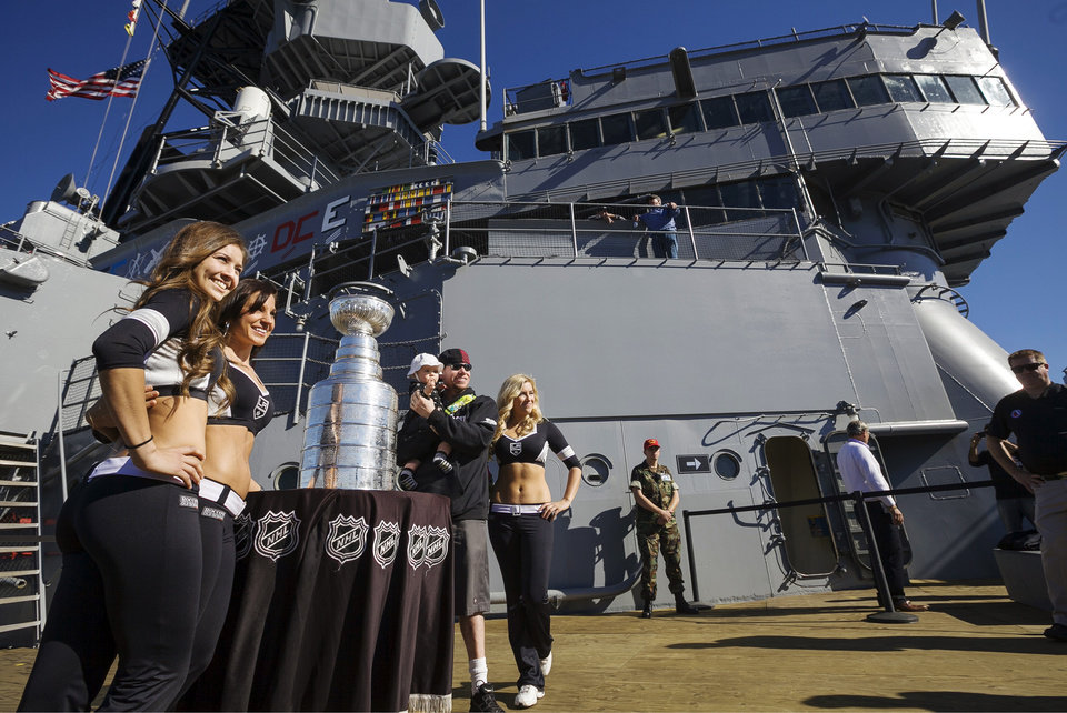 Los Angeles Kings Ice Crew members, from left, Ally, Arsee and Jessica stand with fan Charles Bryant, from Torrance, Calif., and his daughter, Cailey, 1, center, as they pose for photos with the Stanley Cup on tour at the USS Iowa in Los Angeles, Wednesday, Jan. 16, 2013. Hockey\'s top prize was presented to the Kings, who defeated the New Jersey Devils four games to two in the NHL hockey Stanley Cup finals last June. (AP Photo/Damian Dovarganes)