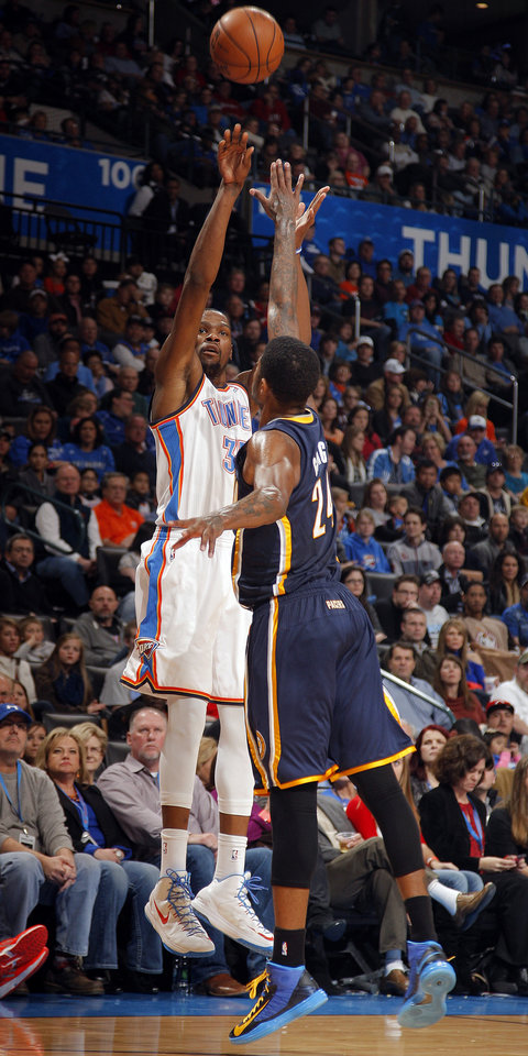 Photo - Oklahoma City's Kevin Durant (35) shoots over Indiana's Paul George (24) during the NBA game between the Indiana Pacers and the Oklahoma City Thunder at the Chesapeake Energy Arena   Sunday,Dec. 9, 2012. Photo by Sarah Phipps, The Oklahoman