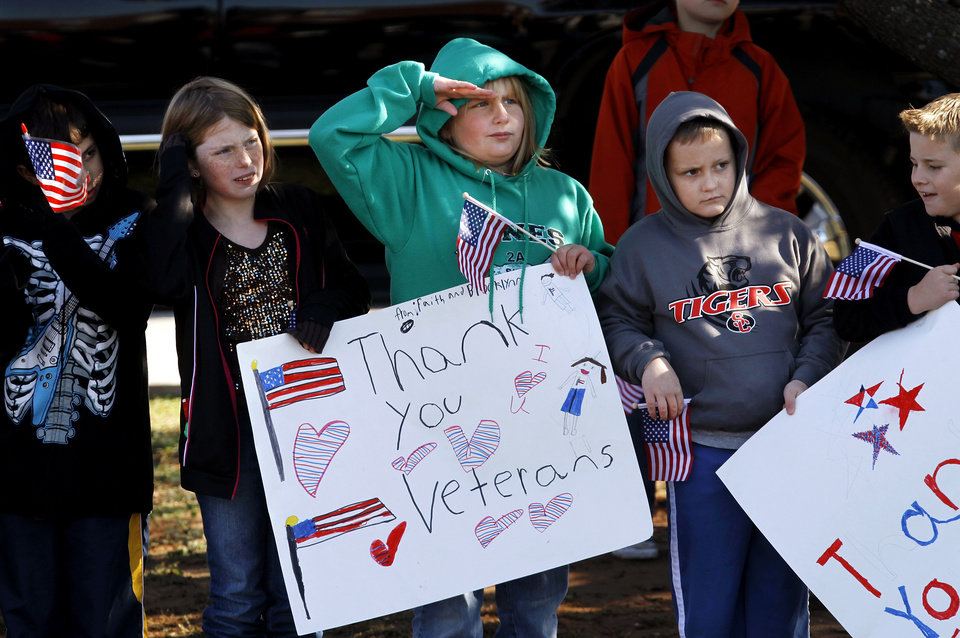 Photo - A student from Soldier Creek Elementary School salutes a patriotic float as it passes in front of school children on Douglas Blvd.  The city of Midwest City teamed with civic leaders and local merchants to display their appreciation for veterans and active military forces by staging a hour-long Veteran's Day parade that stretched more than a mile and a half along three of the city's busiest streets Monday morning, Nov. 12, 2012. Hundreds of people lined the parade route, many of them waving small American flags that had ben distributed by volunteers who marched near the front of the parade. A fly-over performed by F-16s from the138th Fighter Wing, Oklahoma Air National Guard unit in Tulsa thrilled spectators. Five veterans representing military personnel who served in five wars and military actions served as  Grand Marshals for the parade. Leading the parade was the Naval Reserve seven-story American flag, carried by 100 volunteers from First National Bank of Midwest City, Advantage Bank and the Tinker Federal Credit Union. The flag is 50 feet by 76 feet, weighs 110 pounds and was sponsored by the MWC Chapter of Disabled American Veterans. Photo by Jim Beckel, The Oklahoman