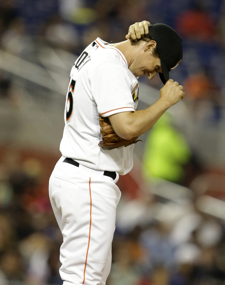 Photo - Miami Marlins starting pitcher Kevin Slowey adjusts his cap after giving up a walk to Washington Nationals' Danny Espinosa during the fifth inning of the MLB National League baseball game, Monday, April 14, 2014, in Miami. (AP Photo/Lynne Sladky)