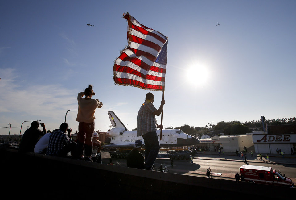 Photo -   Roni Lopez, center, holds an American flag as the space shuttle Endeavour slowly moves along city streets on a 160-wheeled carrier in Los Angeles, Saturday, Oct. 13, 2012 toward its retirement home at a museum. (AP Photo/Jae C. Hong)