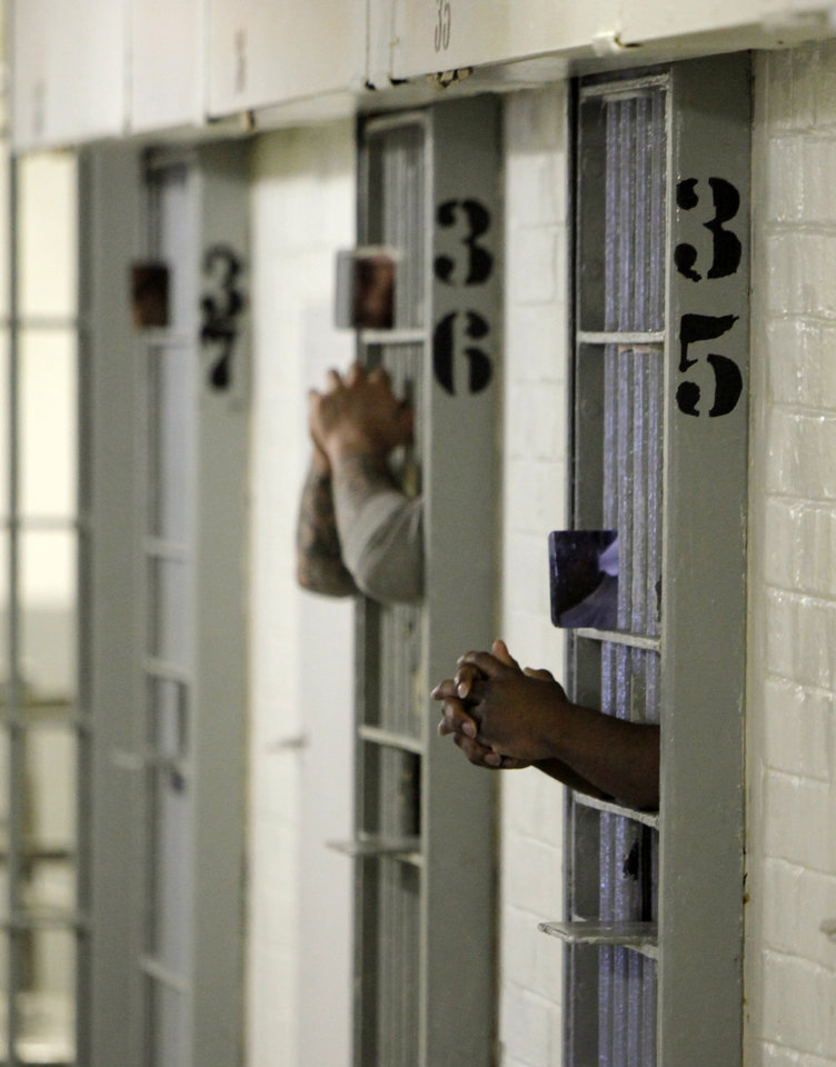 Inmates stick their arms through the bars in the F Cellhouse at the Oklahoma State Penitentiary in McAlester, Okla., Wednesday, Dec. 7, 2011. Photo by Nate Billings, The Oklahoman