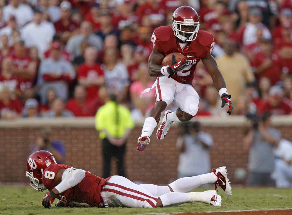 Photo - Oklahoma's Roy Finch (22) leaps over Dominique Whaley (8) during a college football game between the University of Oklahoma Sooners (OU) and the Kansas State University Wildcats (KSU) at Gaylord Family-Oklahoma Memorial Stadium, Saturday, September 22, 2012. Photo by Bryan Terry, The Oklahoman