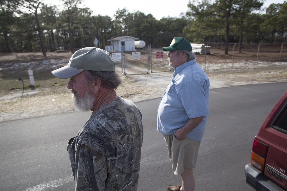 Photo - Flemington Road community resident Sam Malpass, left, and Kenneth Sandlin of Wilmington, North Carolina, stand outside the well water treatment plant that services their homes on Wednesday, Feb. 19, 2014. The neighbors are part of the small community nearby the L.V. Sutton Complex operated by Duke Energy they feel could be polluting well water with spill off and seepage from large coal ash ponds.   (AP Photo/Randall Hill)