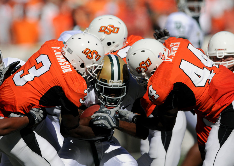 Photo - OSU: Baylor running back Mikail Baker, center, is tackled by a gang of Oklahoma State University defenders including safety Victor Johnson (3), left, and linebacker Donald Booker (44), right,  during the second half of an NCAA college football game in Stillwater, Okla. at Boone Pickens Stadium Saturday, Oct. 18, 2008. Eighth-ranked Oklahoma State defeated Baylor 34-6. (AP Photo/Brody Schmidt) ORG XMIT: OKBS106