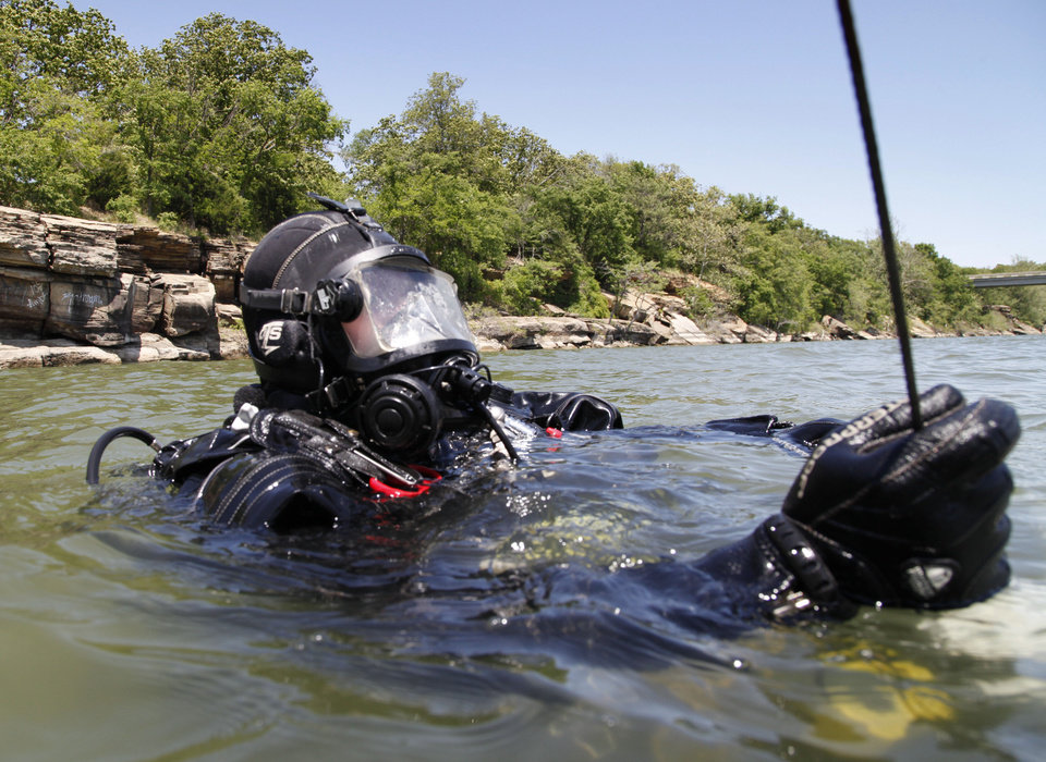 Photo - Patrolman Darrell Splawn prepares to submerge as the Oklahoma Highway Patrol Dive Team spends the day floating a submerged boat and car from the bottom of Lake Tenkiller near Gore, OK, as part of ongoing training exercises, Tuesday, May 6, 2014,  Photo by Paul Hellstern, The Oklahoman