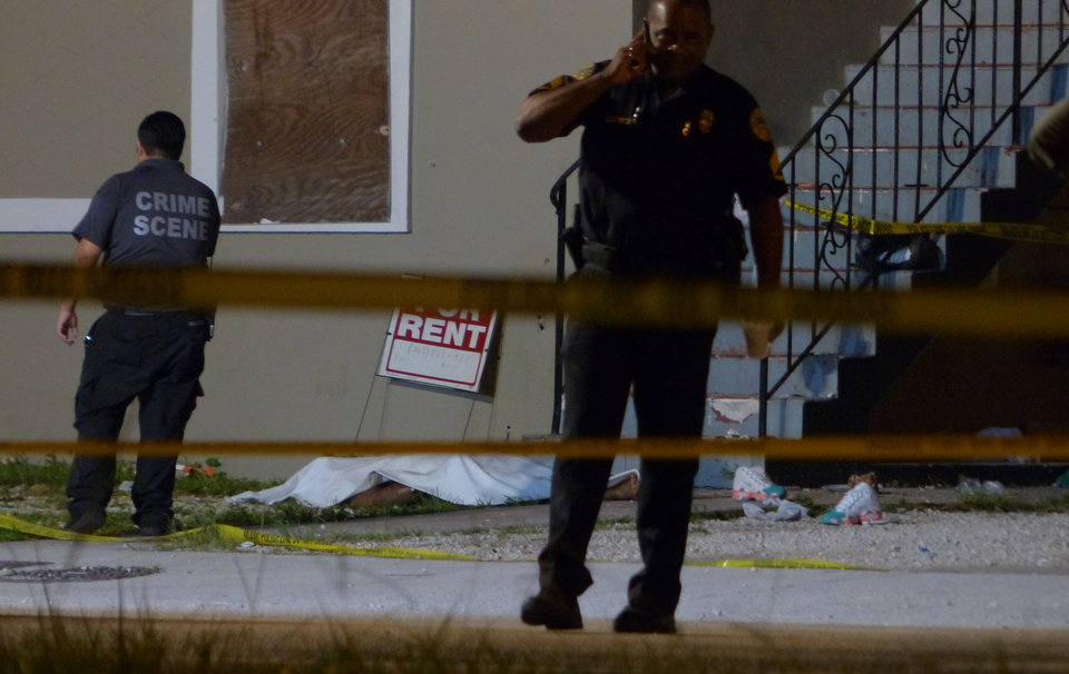 Photo - Authorities work the scene where at least two people were killed and multiple others wounded following a shooting early Tuesday, June 24, 2014, in Miami's Liberty City neighborhood. Miami City Manager Daniel Alfonso said the dead include a 20-year-old man and a teenage girl. (AP Photo/The Miami Herald, Walter Michot)