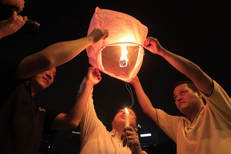 Photo - People prepare to release a sky lantern during a candlelight vigil for passengers aboard a missing Malaysia Airlines plane in Kuala Lumpur, Malaysia, Monday, March 10, 2014. The search operation for the missing Malaysia Airlines Flight MH370 which has involved 34 aircraft and 40 ships from several countries covering a 50-nautical mile radius from the point the plane vanished from radar screens between Malaysia and Vietnam continues after its disappearance since Saturday.  (AP Photo/Lai Seng Sin)
