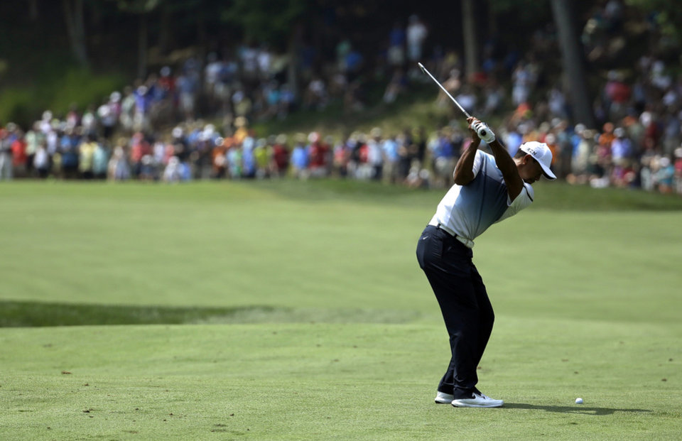 Photo - Tiger Woods hits from the fairway on the second hole during a practice round for the PGA Championship golf tournament at Valhalla Golf Club on Wednesday, Aug. 6, 2014, in Louisville, Ky. The tournament is set to begin on Thursday. (AP Photo/Jeff Roberson)