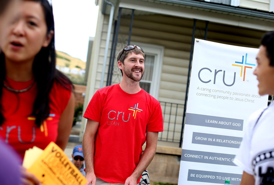 Photo -       Nate Tunnell, minister and director of Cru, center, and Julie Chang, left, greet incoming students at the University of Utah in Salt Lake City on Friday, Aug. 22, 2014. (Laura Seitz, Deseret News)