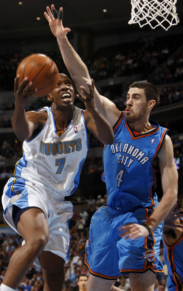 Photo - Denver Nuggets guard Chauncey Billups, left, drives the lane for a shot past Oklahoma City Thunder forward Nick Collison in the third quarter of the Nuggets' 122-112 victory in an NBA basketball game in Denver on Wednesday, April 8, 2009. (AP Photo/David Zalubowski) ORG XMIT: CODZ106