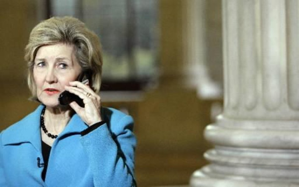 Photo - Sen. Kay Bailey Hutchison, R-Texas, talks on the phone about the shooting at  Fort  Hood, Texas, on Capitol Hill in Washington Thursday, Nov. 5, 2009. (AP Photo/Alex Brandon)