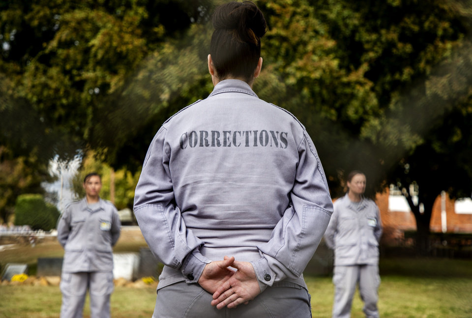 Photo - Member of the Dr. Eddie Warrior Correctional Facility Regimented Treatment Program line the sidewalk for the women being released from the facility on Monday, Nov. 4, 2019 in Taft, Okla. Governor Kevin Stitt greeted an estimated 70 women whose sentences he commuted from the facility. [Chris Landsberger/The Oklahoman]