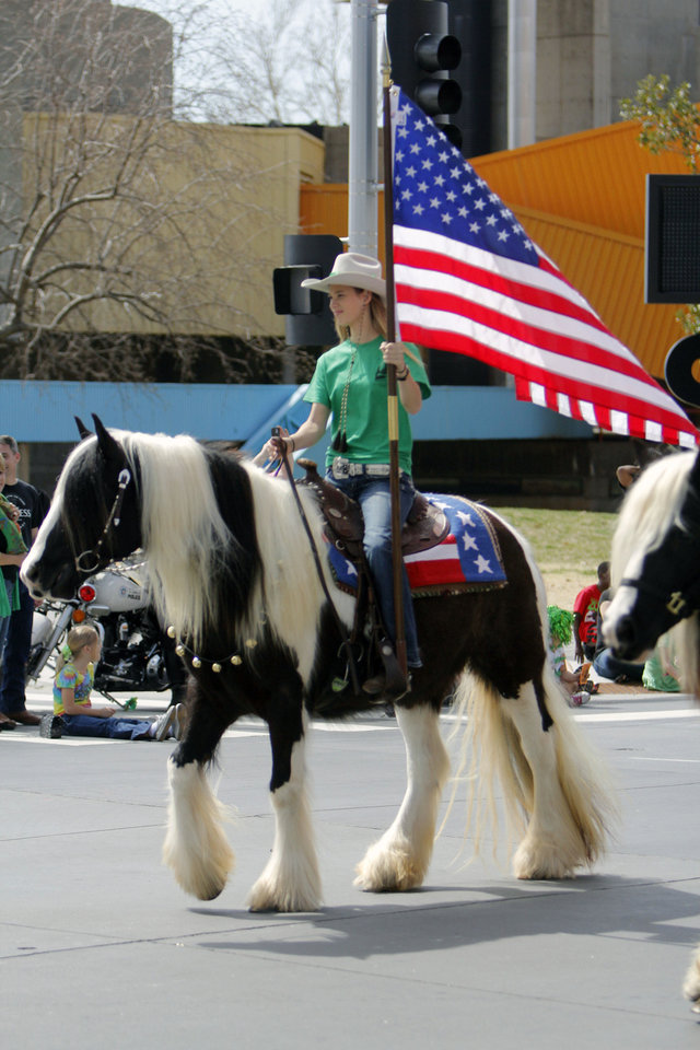Above: Macey Murselley carries a flag for Deerinwater Farms on Saturday during the St. Patrick's Day Parade in downtown Oklahoma City.