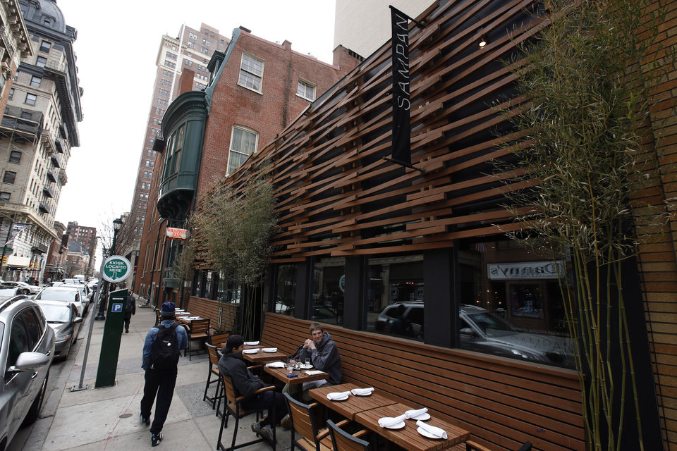 In this April 1, 2014 photo, patrons sit outside of Sampan, a contemporary Asian restaurant, along 13th Street in Philadelphia. Tourism officials will tell you the restaurant-rich area in the heart of downtown is called Midtown Village, but that moniker hasn't entirely caught on with locals. Philadelphia food lovers just know 13th Street as a vibrant area chock full of great eateries and wine bars. (AP Photo/Matt Slocum)