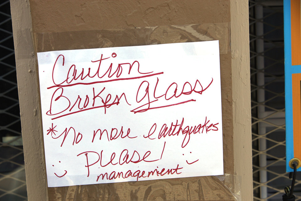 Photo -  Sign on Carolyn Deal's business Country Vapor warning of the broken window from an early morning earthquake in Harrah on Tuesday. Photo by David McDaniel, The Oklahoman   David McDaniel