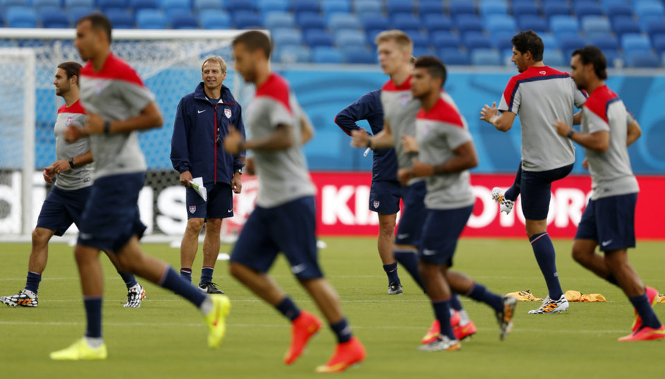 Photo - United States' head coach Jurgen Klinsmann, back left, looks on as his team warms up during an official training session the day before the group G World Cup soccer match between Ghana and the United States at the Arena das Dunas in Natal, Brazil, Sunday, June 15, 2014.  (AP Photo/Julio Cortez)
