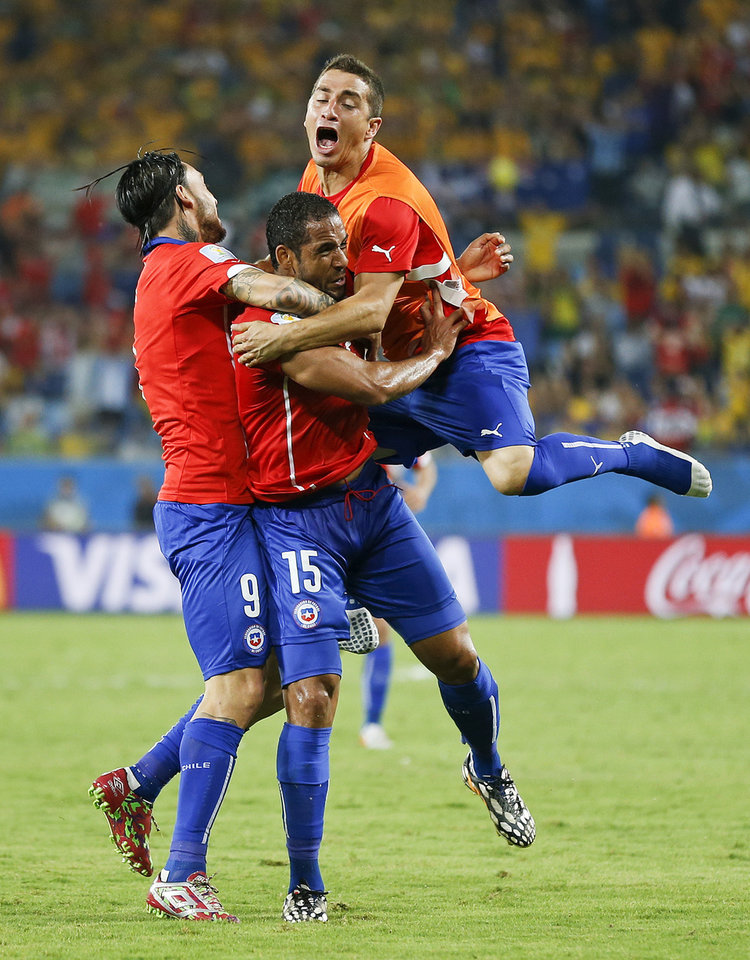 Photo - Chile's Jean Beausejour, center, celebrates with teammates after scoring his side's third goal during the group B World Cup soccer match between Chile and Australia in the Arena Pantanal in Cuiaba, Brazil, Friday, June 13, 2014.  (AP Photo/Frank Augstein)