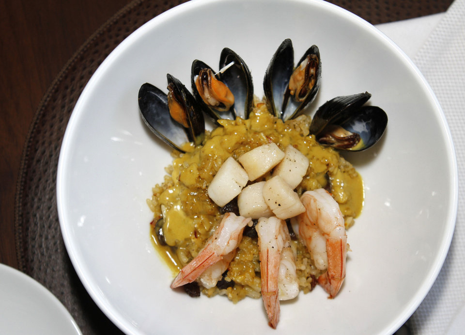 Photo - This seafood dish from Vast is a play on classic Paella, and includes bay scallops, shrimp and mussels in a Thai-inspired sauce with rice. Photo by Steve Gooch, The Oklahoman  Steve Gooch - The Oklahoman